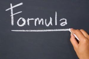 Hand writing formula on blackboard